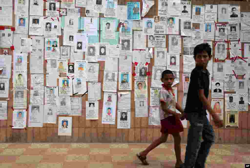 Two youths walk past a wall pasted with flyers showing some of the missing on Monday April 29, 2013 in Savar, near Dhaka, Bangladesh.