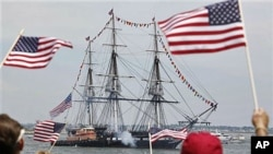 Spectators wave flags as the USS Constitution fires its cannons off Castle Island in Boston, Massachussetts, on its annual 4th of July turn-around in Boston Harbor, July 4, 2011