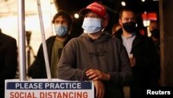 美國紐約民眾在選舉夜戴著口罩觀看選舉結果(路透社2020年11月3日)