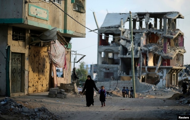 A Palestinian woman walks with her daughter as the remains of a house that witnesses said was destroyed during the 50-day war between the Hamas militant movement and Israel, in the east of Gaza City, Oct. 12, 2014.