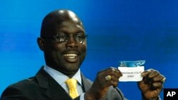 Former player Georges Weah shows the name of Manchester City, who will play Group D, during the UEFA Champions League draw in Monaco, Thursday, Aug. 30, 2012. (AP Photo/Claude Paris)