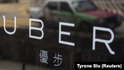 Un taxi se reflète sur une fenêtre des bureaux de Uber à Hong Kong en Chine le 12 août 2015.