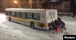 People push a bus on an icy road in Boston, in this still image taken from a Jan. 4, 2018, social media video. Karen Lyons Clauson/via Reuters