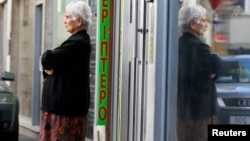 A woman waits for the opening of a branch of Laiki Bank in Nicosia, March 29, 2013.