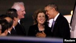 El presidente Barack Obama es recibido en Tokio por la embajadora Caroline Kennedy y su esposo, Edwin Schlossberg y otros funcionarios japoneses.