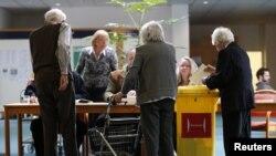 Para pemilih berbincang dengan para petugas pemilu di sebuah TPS sebelum memasukkan surat suara mereka ke dalam kotak suara di Hanovr, negara bagian Lower Saxony (20/1).
