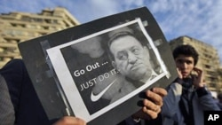 """A protester holds a placard showing Egyptian President Hosni Mubarak and reading """"Go out... Just do it"""" at the continuing anti-government demonstration in Tahrir Square in downtown Cairo, Egypt, February 10, 2011."""