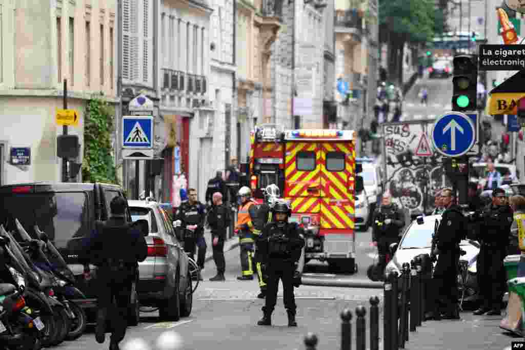 Police officers stand on a street near the site of an ongoing hostage taking in central Paris, France.