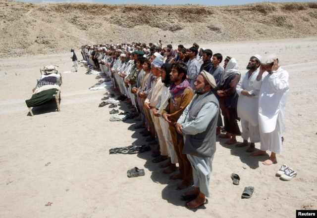 Afghan villagers pray for the victims of a roadside bomb in Laghman province June 3, 2013.
