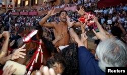 Jockey Jonatan Bartoletti of the Giraffa parish celebrates after winning the Palio di Siena horse race in Siena, Italy, July 2, 2017.