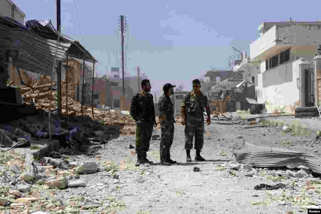 Soldiers loyal to Syrian President Bashar al-Assad stand on a damaged street full of debris in Qusair, June 6, 2013.