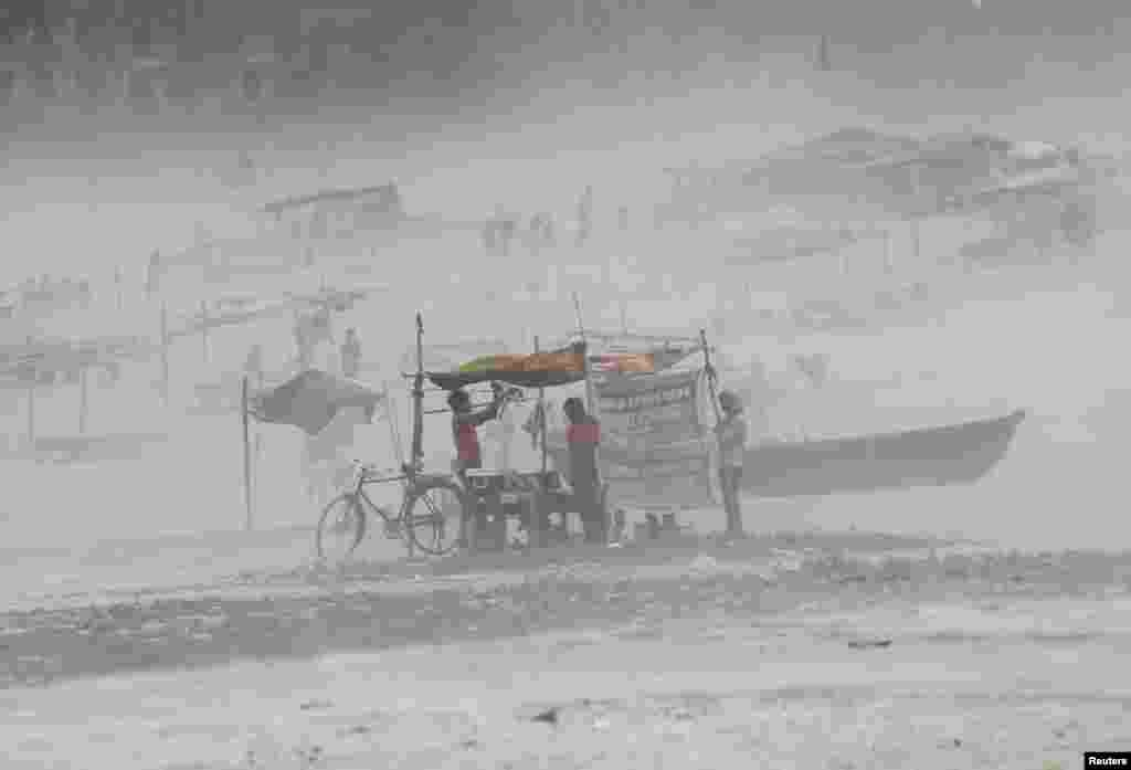 A man fixes a tarpaulin on his stall during a dust storm on the banks of the river Ganges in the northern Indian city of Allahabad.