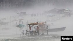 Seorag pria membetulkan terpal di warungnya saat badai menghantam sekitar wilayah Sungai Gangga di Allahabad (13/10).