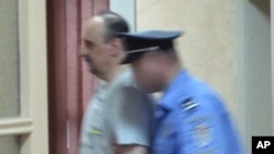 Goran Hadzic (L), a Croatian Serb wartime leader indicted for crimes against humanity during the 1991-95 Croatian war, enters a special court escorted by a policeman in this handout photo taken in Belgrade, July 20, 2011.