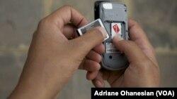 FILE - A mobile phone user in Juba, South Sudan, removes his smartphone battery.