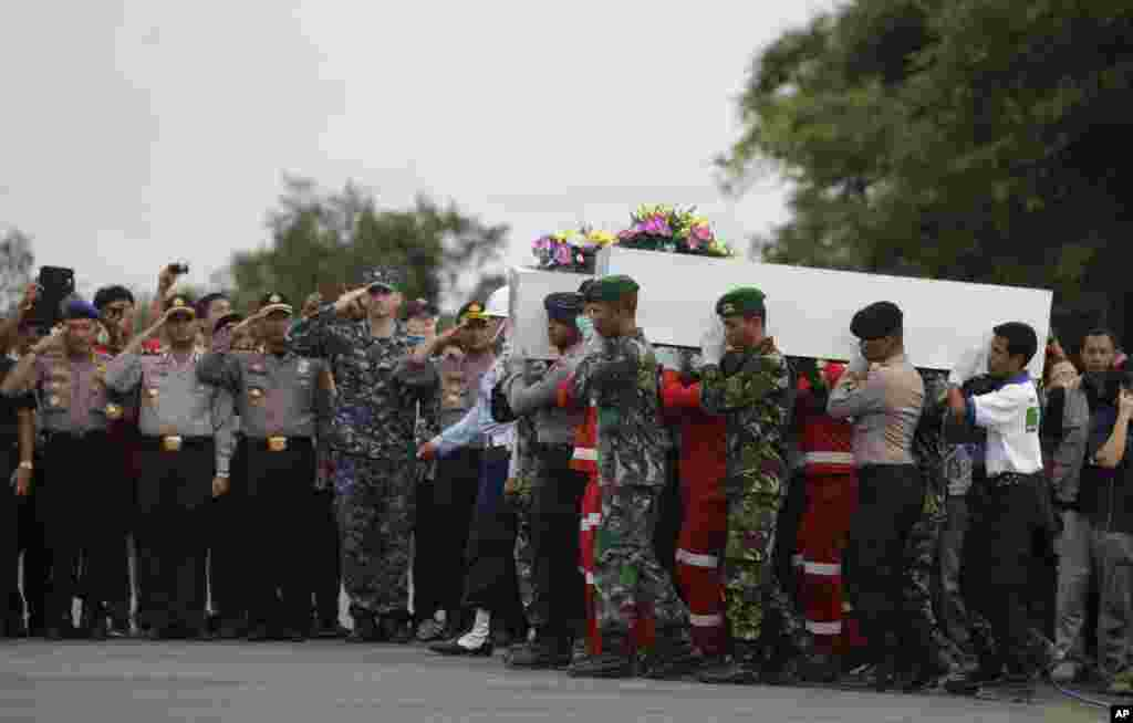 Members of the National Search And Rescue Agency and an Indonesian soldier carry coffins containing bodies of the victims aboard AirAsia Flight 8501 to transfer to Surabaya at the airport in Pangkalan Bun, Indonesia, Jan. 2, 2015.