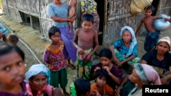 Rohingya Muslims pass time near their shelter at a refugee camp outside Sittwe, Myanmar.