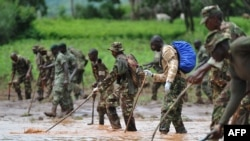 Kenya Defense Force (KDF) soldiers patrol and inspect through mud and debris on May 11, 2018 in search of bodies of victims after a dam burst its banks in Subukia, Nakuru county.