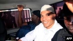 Karim Wade, fils de l'ancien président Abdoulaye Wade (2000-2012), arrive au tribunal entouré d'agents de sécurité à bord d'un véhicule, à Dakar, Sénégal, 31 juillet 2014.