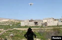 FILE - A female Kurdistan Workers Party (PKK) fighter waits for a drone to land, in Sinjar, March 11, 2015. The drone had flown to check enemy positions near a site which had been hit by two Islamic State car bombs.