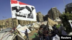 "Anti-Mursi protesters sit outside their tents, below a flag that reads, ""No, to Constitution"" at Tahrir Square in Cairo December 10, 2012. The Egyptian government has given the military the authority to arrest civilians to help safeguard a constitutional"