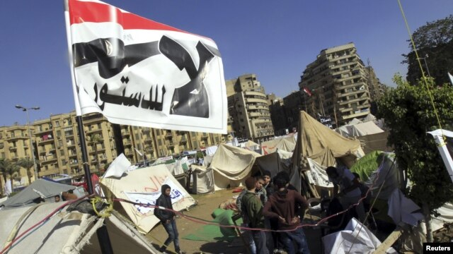 """Anti-Mursi protesters sit outside their tents, below a flag that reads, """"No, to Constitution"""" at Tahrir Square in Cairo December 10, 2012. The Egyptian government has given the military the authority to arrest civilians to help safeguard a constitutional"""