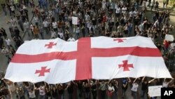 Georgian demonstrators carry a state flag during a protest rally against prison abuse in Tbilisi, Georgia, Sept. 20, 2012