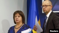 FILE - Ukraine's Prime Minister Arseny Yatseniuk and Finance Minister Natalia Yaresko leave a news conference in Kyiv, Ukraine, Oct. 15, 2015.
