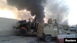 Musul'daki çatışmalarda ateşe verilen bir Irak zırhlı aracı