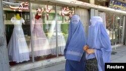 افغان خواتین عروسی لباس فروخت کرنے والی ایک دکان کے سامنے سے گزر رہی ہیں۔