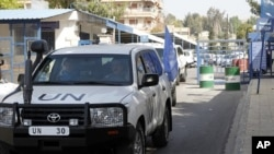 United Nations (UN) observers traveling in UN vehicles leave the UN office in Damascus, April 26, 2012