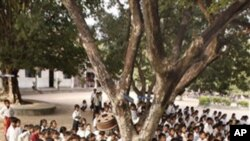 Cambodian school children sit under the shade of tree as they listen to teacher at Trapaing Loeuk primary school in Kampong Speu province.