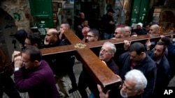 Feligreses cristianos portan un cruz mientras caminan por la Vía Dolorosa, en la Ciudad Vieja de Jerusalén, el vienres, 30 de marzo, de 2018, durante la celebración del Viernes Santo.