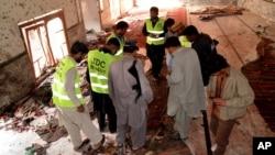 30일 파키스탄 시카르푸르의 이슬람 시아파 사원에서 폭탄 테러가 발생한 가운데, 조사관들이 사고 현장을 살피고 있다.