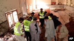 Des enquêteurs et autorités de la sécurité font des investigations à la mosquée touchée par un attentat meurtrier venredi 30 janvier (2015) à Shikarpur, Pakistan.