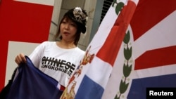A protester, carrying a former Hong Kong colonial flag, demonstrates against China's intervention and control of the internal affairs of the former British colony, outside the British Consulate in Hong Kong June 15, 2014