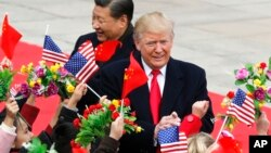 U.S. President Donald Trump, right, and Chinese President Xi Jinping are greeted by children waving flowers and flags during a welcome ceremony at the Great Hall of the People in Beijing, Nov. 9, 2017.