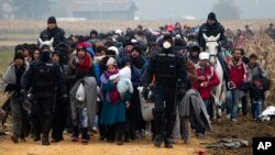 Escorted by police, migrants move through fields after crossing from Croatia, in Rigonce, Slovenia, Oct. 27, 2015.