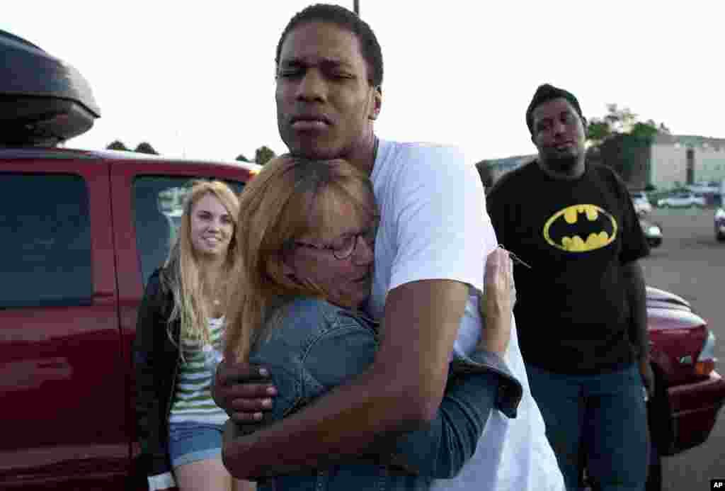 Judy Goos, second from left, hugs her daughter's friend, Isaiah Bow, 20, while eye witnesses Emma Goos, 19, left, and Terrell Wallin, 20, right, gather outside Gateway High School where witnesses were brought for questioning July 20, 2012 in Denver.