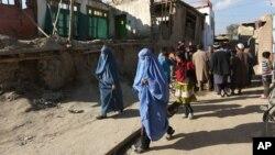 阿富汗妇女走向因地震被损坏的房屋(2015年10月26日)。