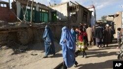 Beberapa perempuan Afghanistan berjalan melewati rumah-rumah yang hancur akibat gempa diKabul, Afghanistan (26/10).