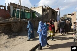 FILE - Afghan women walk towards a damaged house following an earthquake, in Kabul, Afghanistan, Monday, Oct. 26, 2015.