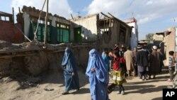 阿富汗婦女走向因地震被損壞的房屋(2015年10月26日)