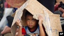 一个男孩在菲律宾中部城市塔克洛班的机场冒雨等待撤离。