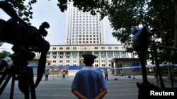 FILE - A policeman guards the entrance of the Jinan Intermediate People's Court in Jinan, Shandong province, Aug. 26, 2013.