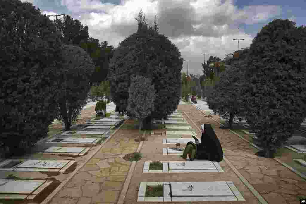An Iranian woman prays at the graves of unknown soldiers who were killed during 1980-88 Iran-Iraq war, at the Behesht-e-Zahra cemetery just outside Tehran, March 20, 2017, on the eve of the Iranian New Year, or Nowruz.