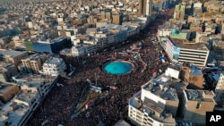 In this aerial photo released by an official website of the office of the Iranian supreme leader, mourners attend a funeral ceremony for Iranian Gen. Qassem Soleimani and his comrades, who were killed in Iraq in a U.S. drone strike on Friday, in Tehran, I