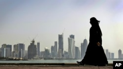 FILE - In this May 14, 2010 file photo, a Qatari woman walks in front of the city skyline in Doha, Qatar.
