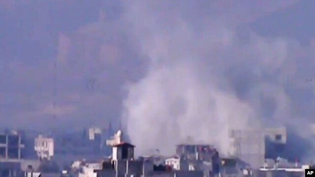 In this image from video obtained from the Shaam News Network, smoke rises due to shelling in the Damascus countryside, Jan. 2, 2013.