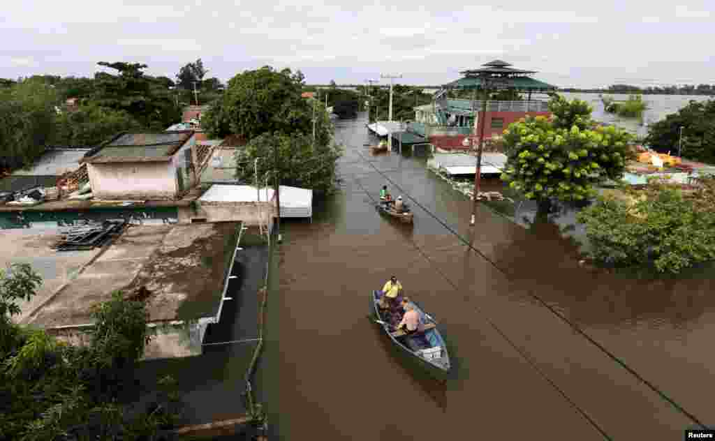Men travel on a boat near flood-affected houses in Asuncion, Paraguay.More than 100,000 people had to evacuate from their homes in the bordering areas of Paraguay, Uruguay, Brazil and Argentina due to severe flooding in the wake of heavy summer rains brought on by El Niño, authorities said.